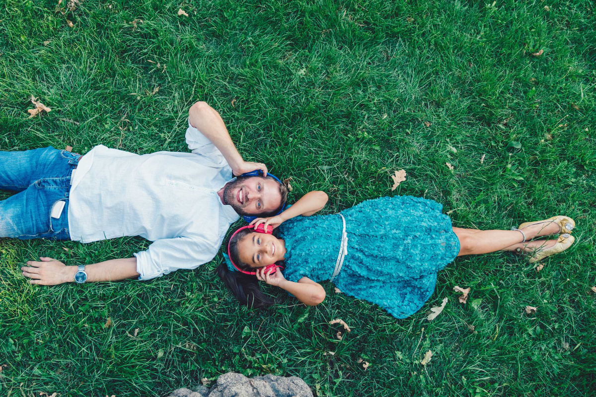 father and daughter lying on grass with headphones on
