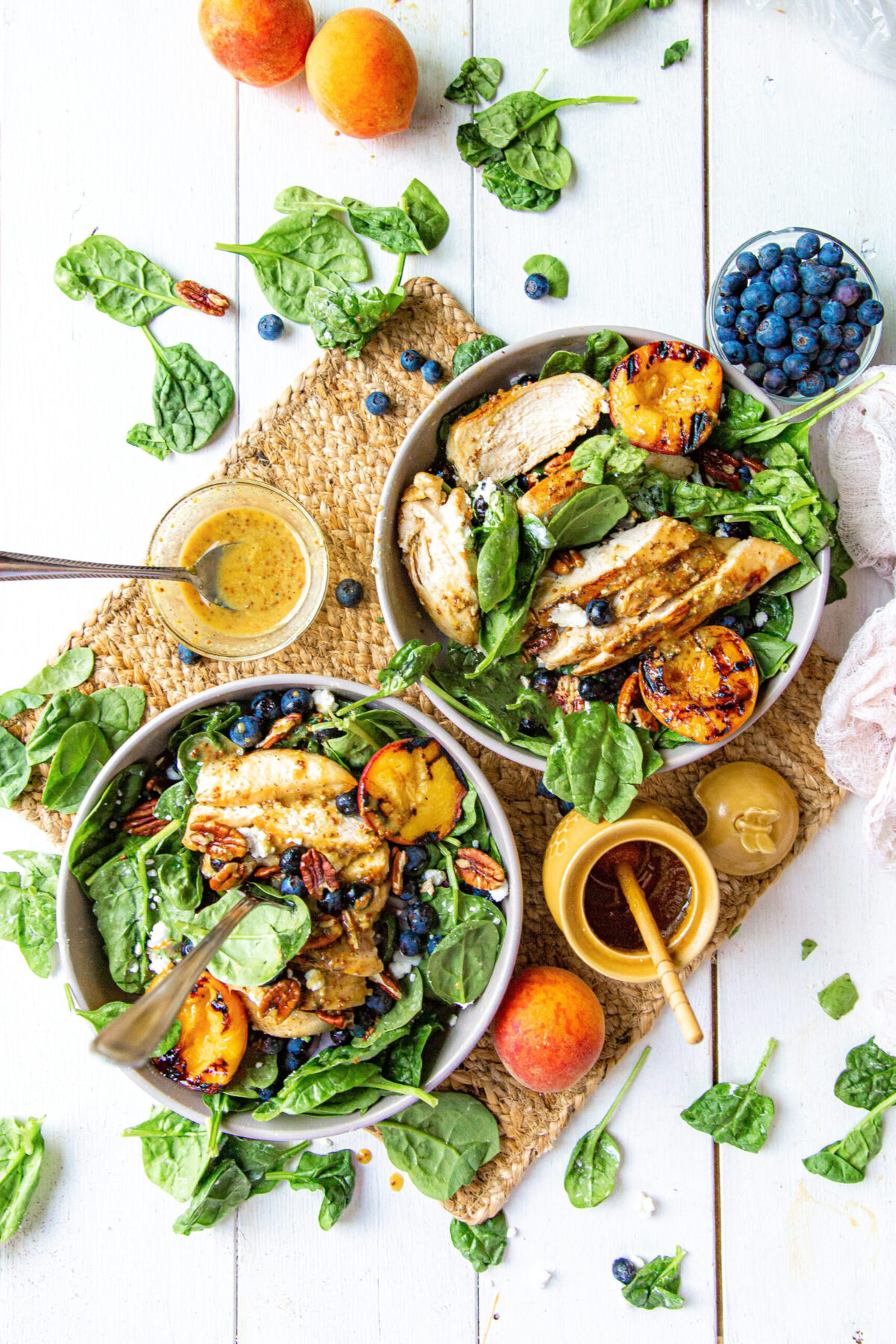 spinach salad with grilled chicken, blueberries and peaches two bowls