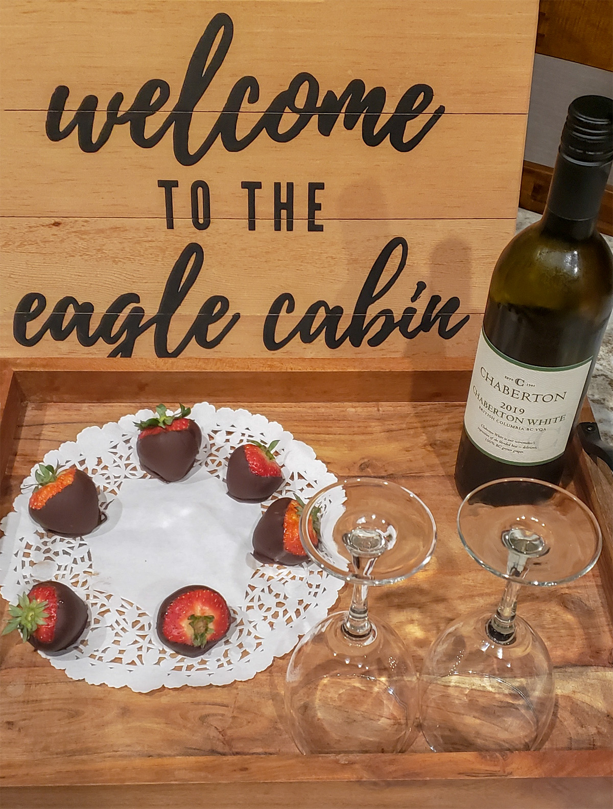 plate of chocolate dipped strawberries, Eagle cabin welcome sign and wine and wine glasses