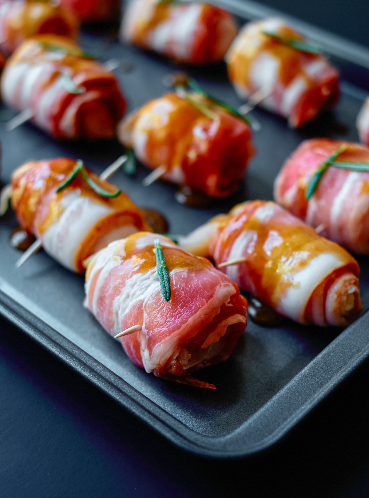 bacon wrapped chicken bites raw on cooking sheet