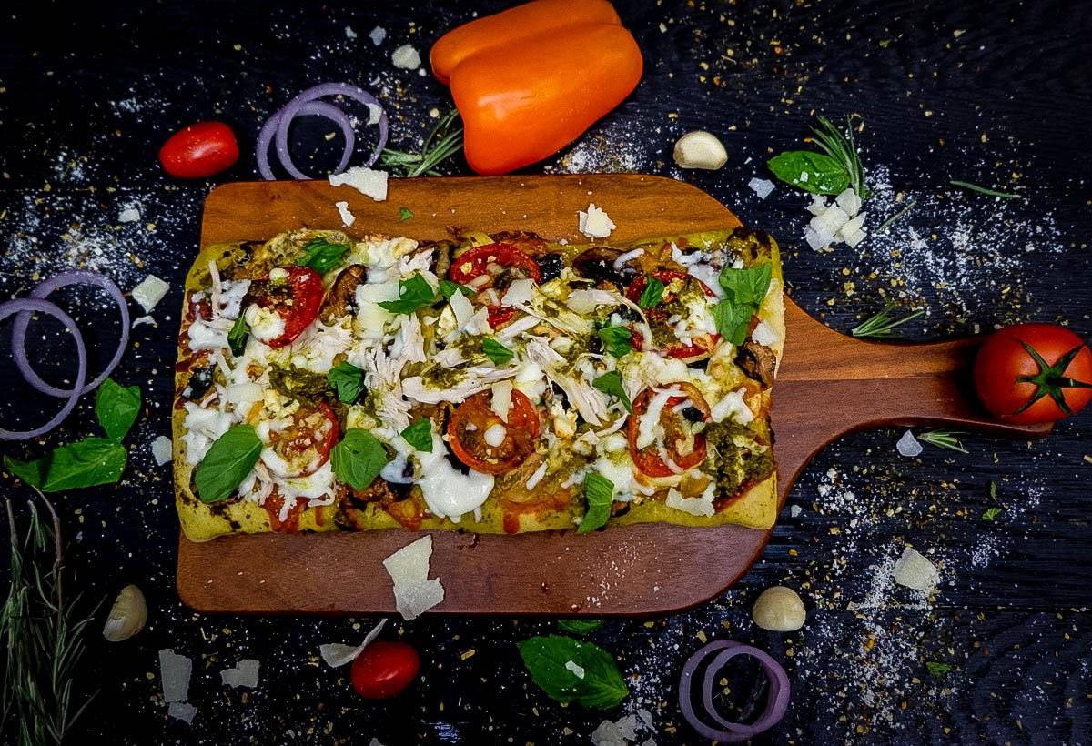 Pesto chicken pizza on a cutting board