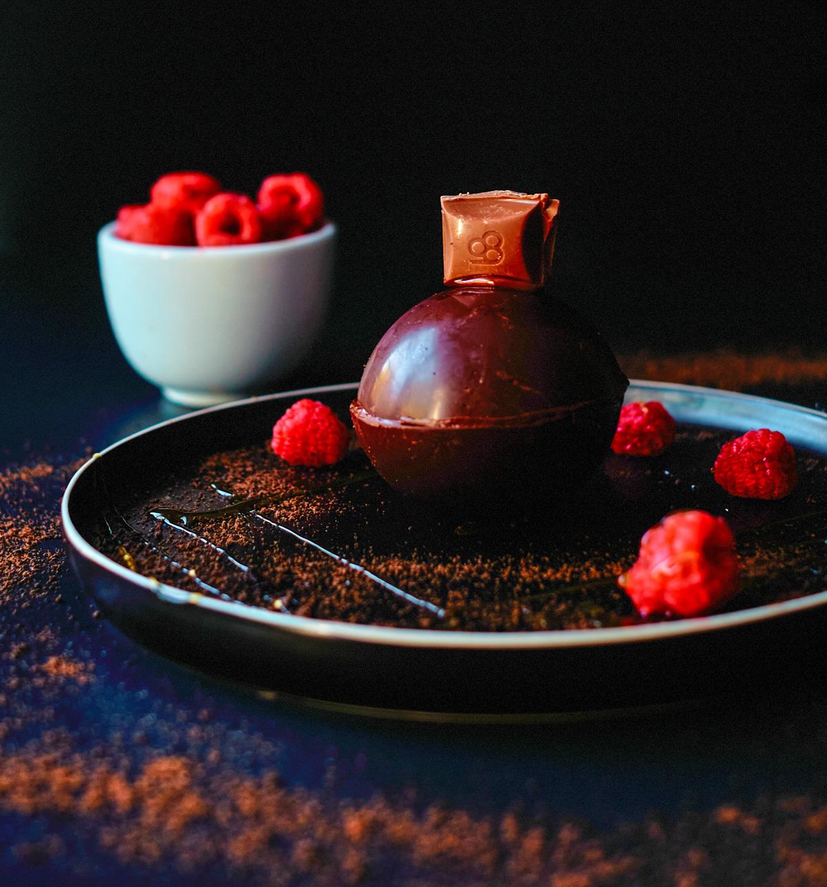 magic chocolate ball with raspberries, caramel sauce and caramilk piece