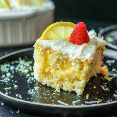 lemon poke cake slice with raspberry on top