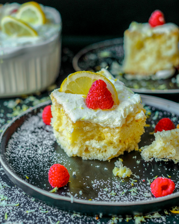 lemon poke cake slice with raspberry on top