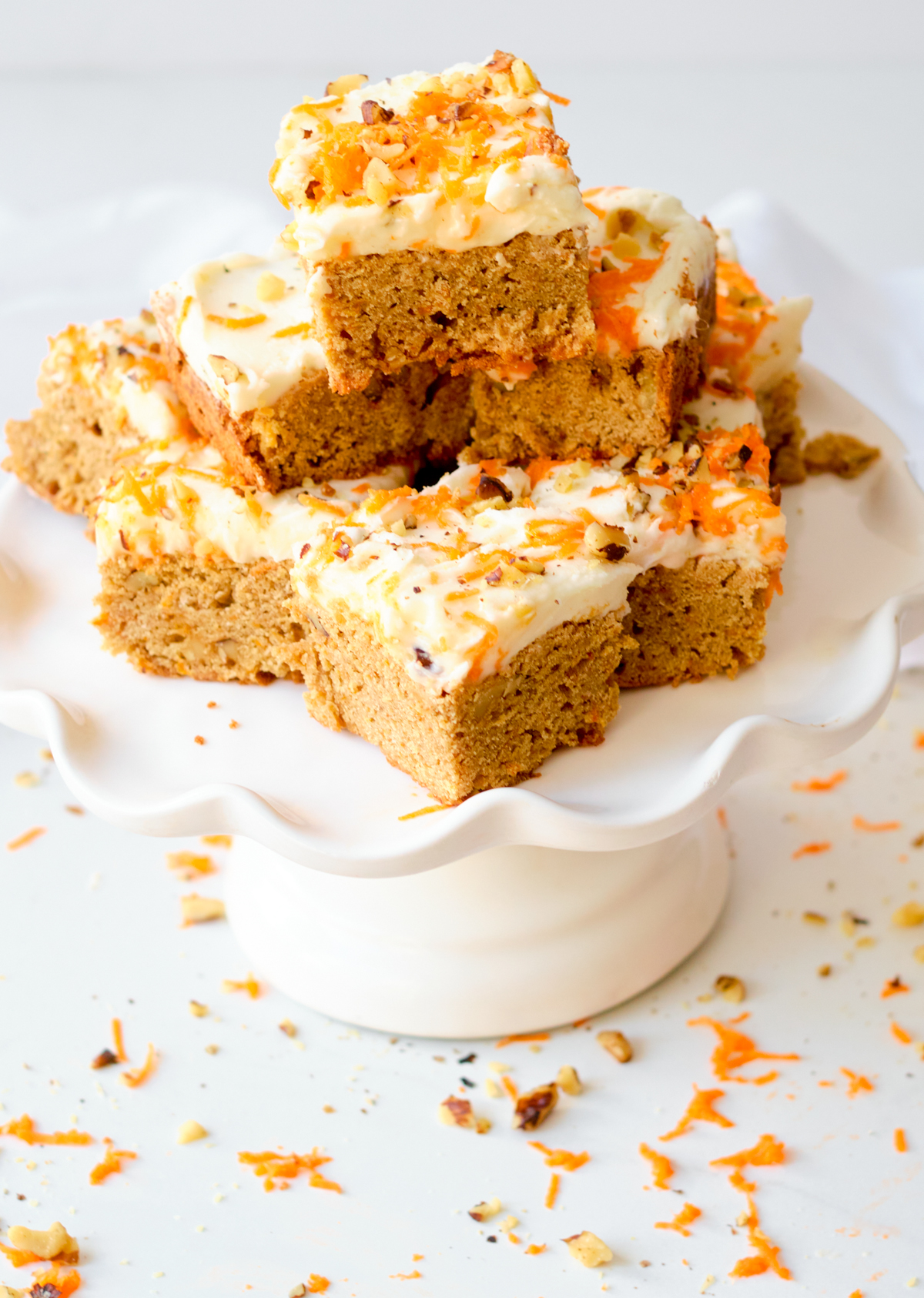 carrot cake blondies squares on a white cake stand
