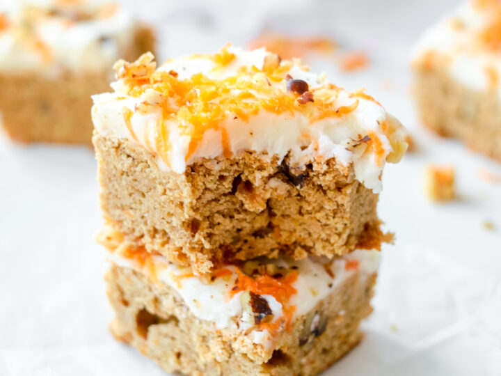 two carrot cake blondies squares stacked top one with a bite in it