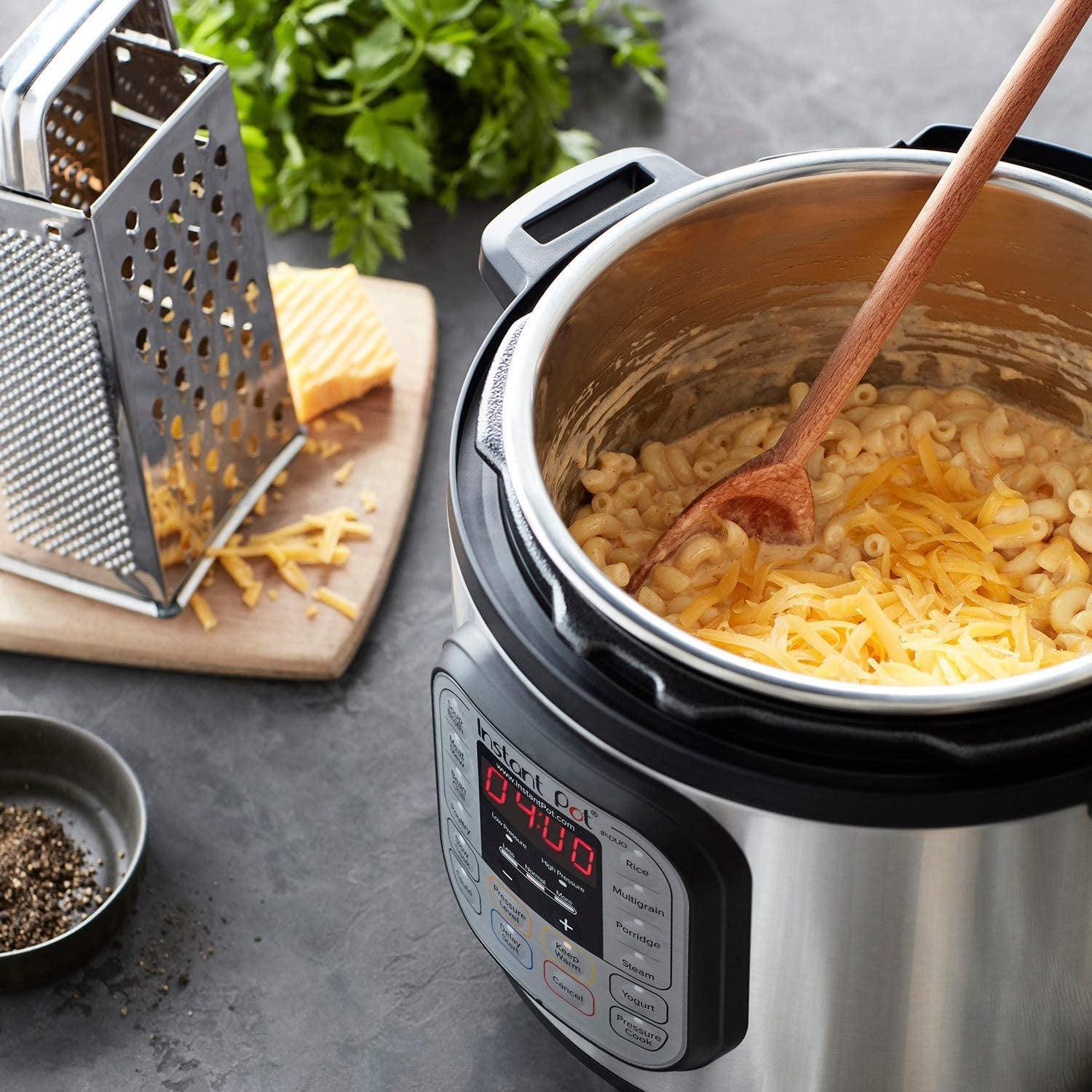 instant pot duo with food inside, cheese grater on the side