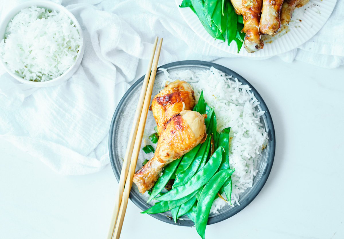 soy sauce drumsticks with sugar peas, white rice and chopsticks on a plate