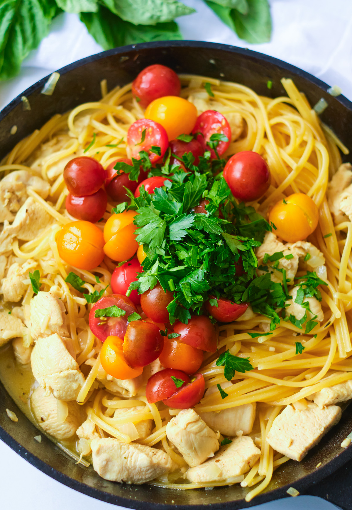 chicken scampi with cherry tomatoes and fresh basil in a cast iron pan