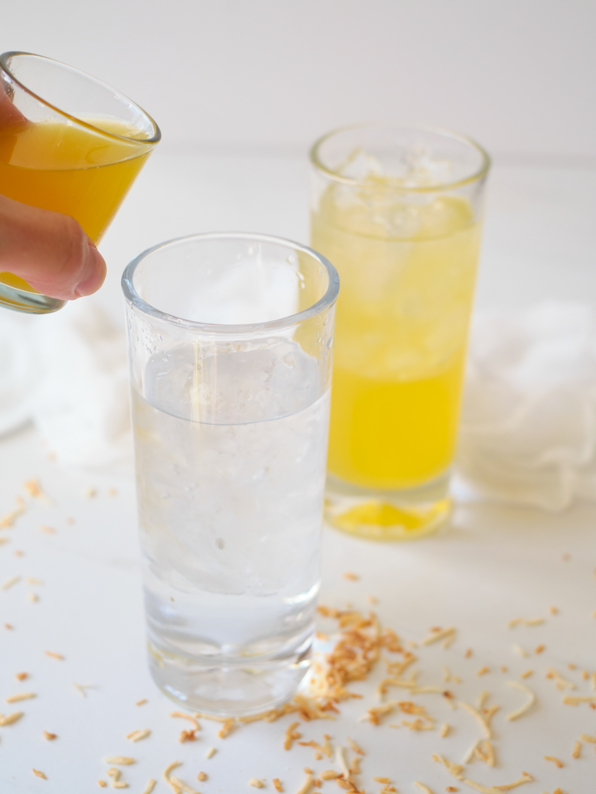 pineapple Italian Soda ingredients glasses with crushed ice, toasted coconut, cream, pineapple juice, club soda