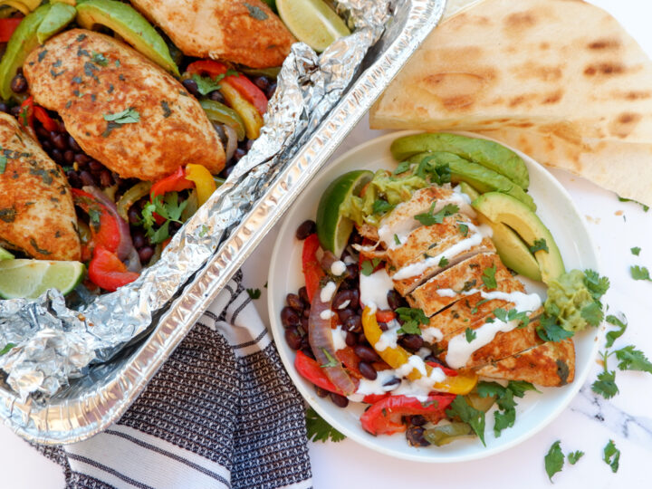 chicken fajita foil packets. Chicken foil packet and plated chicken breast on black beans, bell peppers and avocado on the side