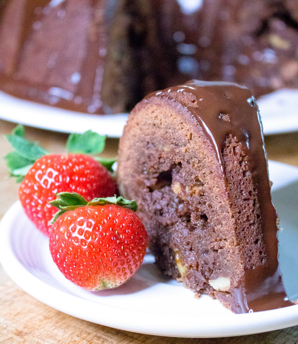 tunnel of fudge cake slice with whole strawberries on the side