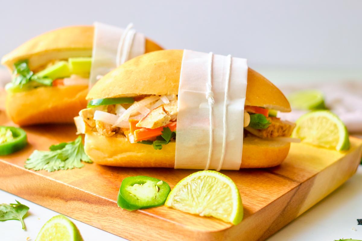 lemongrass chicken banh mi with sriracha mayo on a cutting board