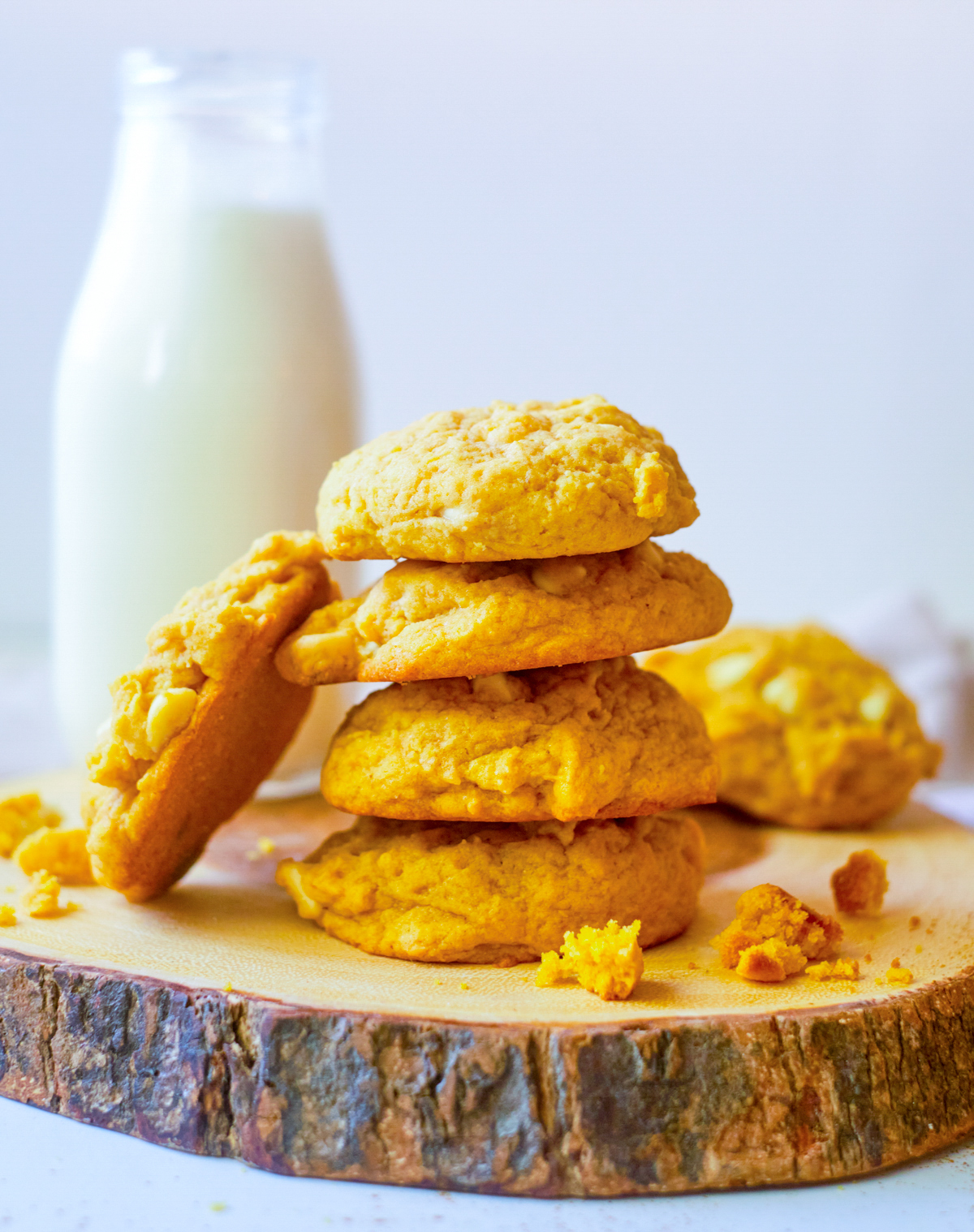 Pumpkin cookies in a stack of 4 with one cookie leaning on stack and jug of milk behind cookies
